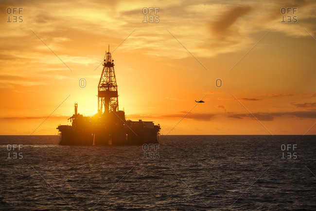 Oil production platform in sea against sky during sunset