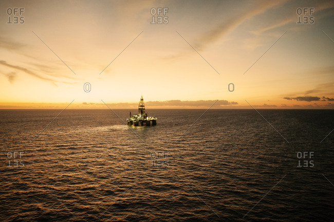 Distant view of oil rig in sea against sky during sunset
