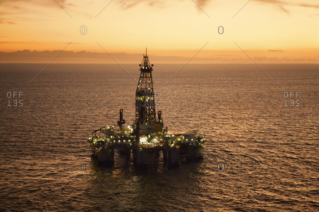 High angle view of oil rig in sea during sunset
