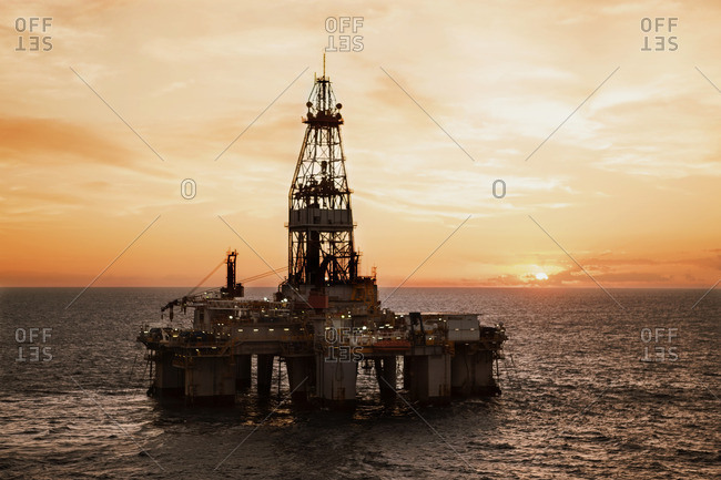 Oil rig in sea against sky during sunset