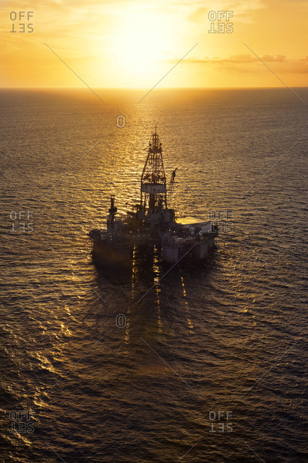High angle view of oil platform in sea during sunset