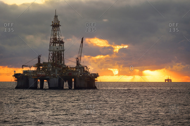 Oil platforms in sea against cloudy sky sunset