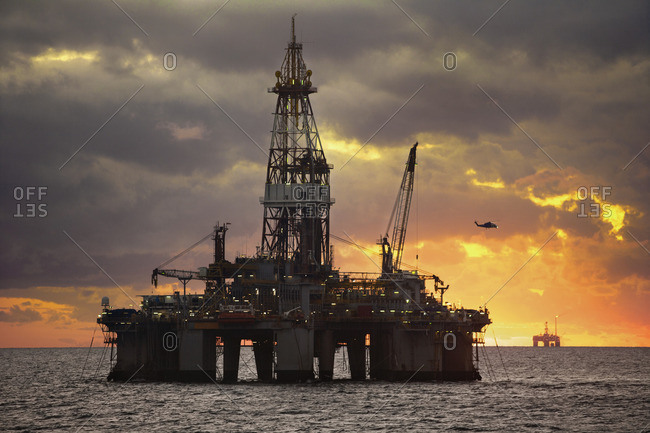 Oil rigs in sea against cloudy sky sunset
