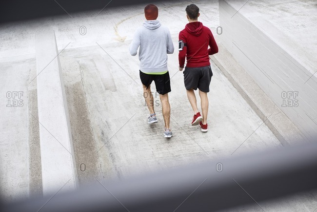 High angle view of male friends running on footpath at parking lot