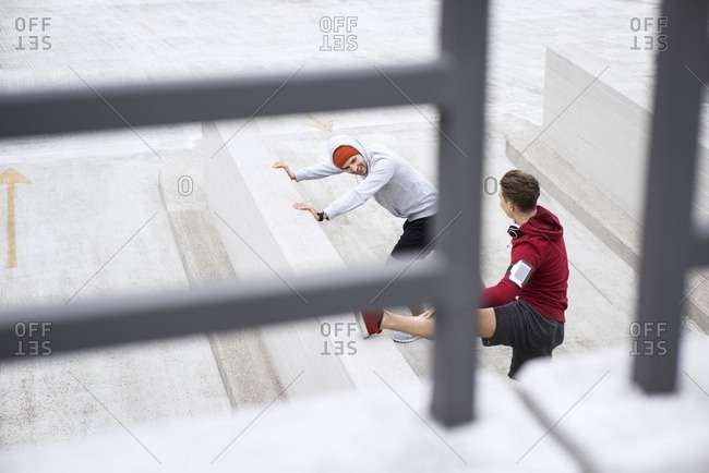 High angle view of male athletes warming up on footpath at parking lot