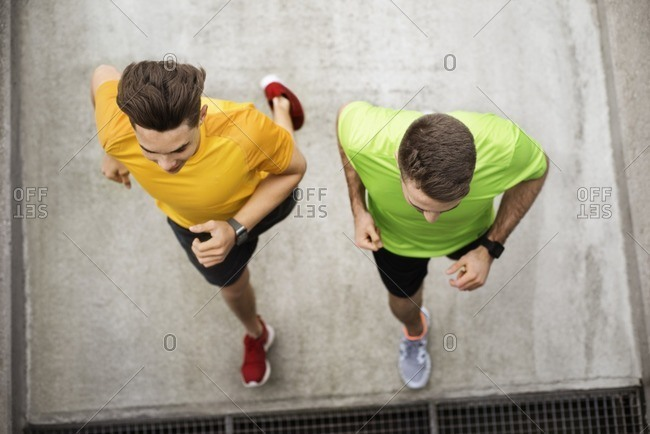 Overhead view of male friends running on footpath at parking lot