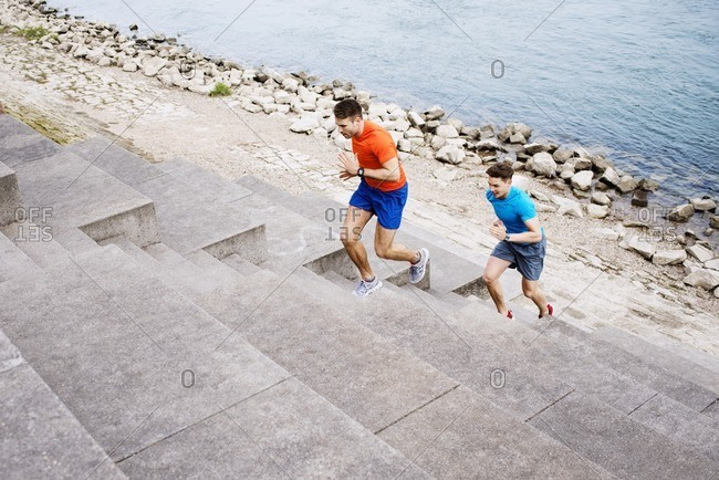 High angle view of male athletes running on steps at beach