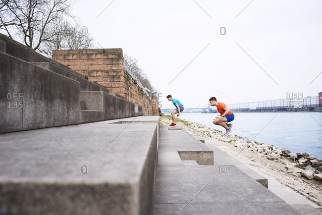Side view of male athletes jumping on steps at beach