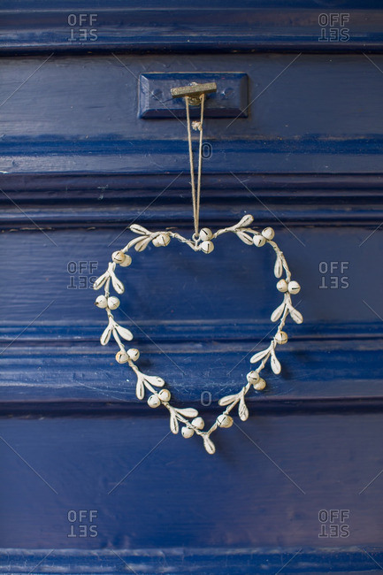 Close-up of a small heart-shaped pendant hanging from a blue wood door
