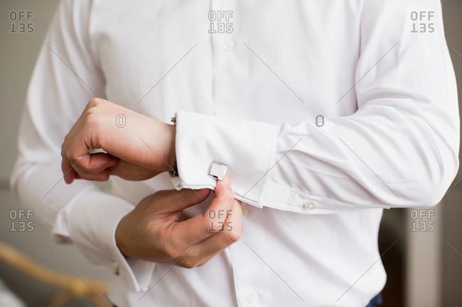 Man adjusting cuff links on his shirt