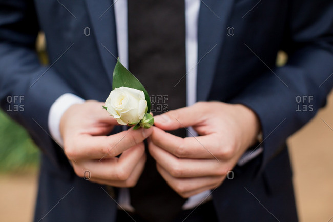 Man in a suit holding a small white rose