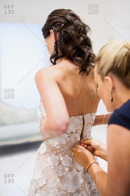 Bride having her wedding dress fastened