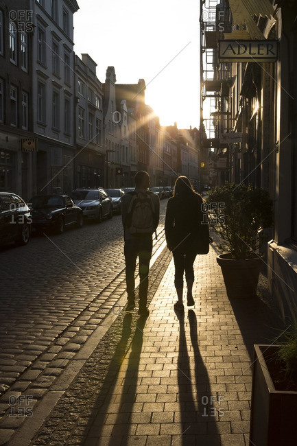 Lubeck, Germany - May 11, 2016: Couple walking on the streets at sunset