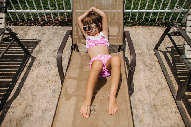 Girl sitting poolside on a chaise lounge chair