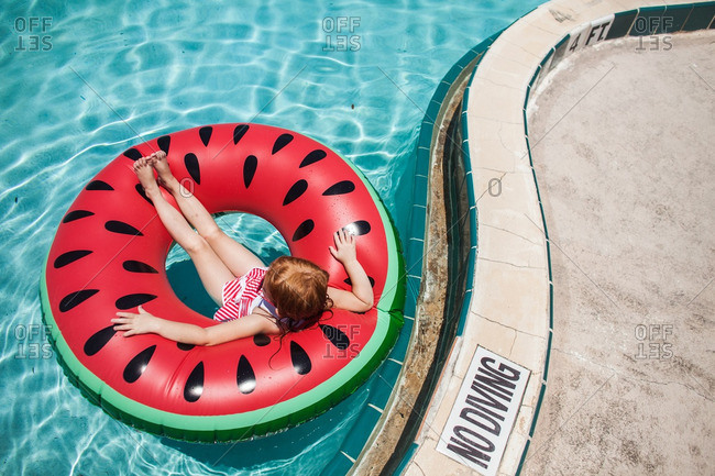 Girl in a swimming pool floating on a watermelon inner tube