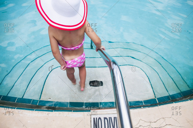 Girl standing on steps along the edge of a swimming pool
