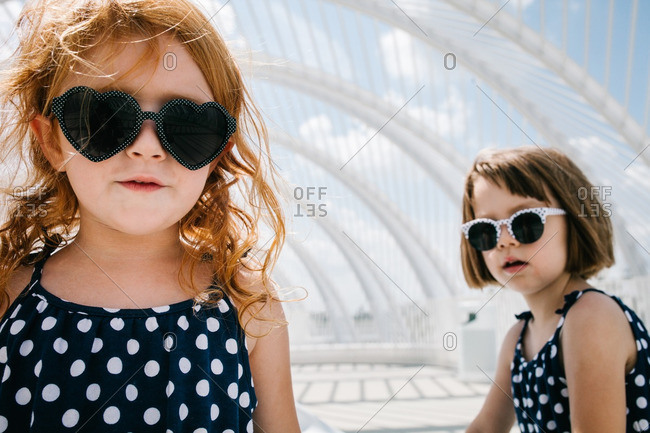 Two girls wearing sunglasses and polka dot sundresses