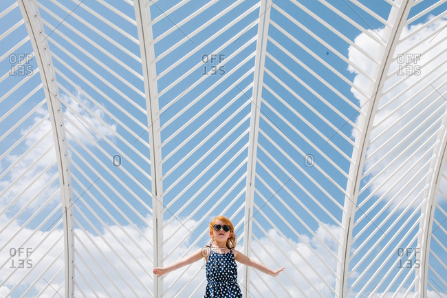 Girl wearing sunglasses and a polka dot dress outside under a trellis