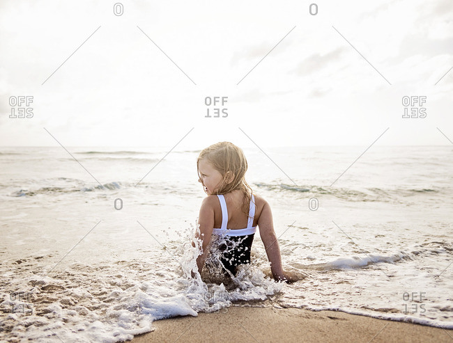 Girl sitting in water on beach