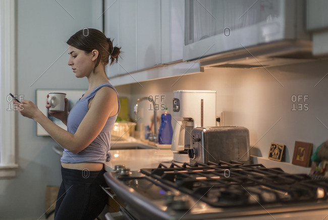 Young woman drinking coffee and texting on phone in her kitchen