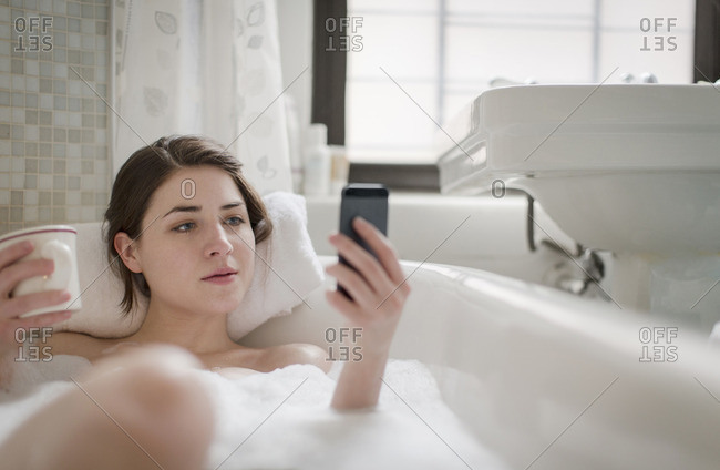 Young woman in a bathtub on her cell phone