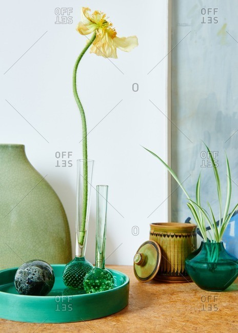 Still life tabletop display with vintage glass vases and ceramics