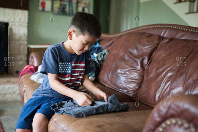 Boy folding laundry while seated on the couch