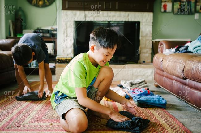 Boys helping fold the laundry on the floor