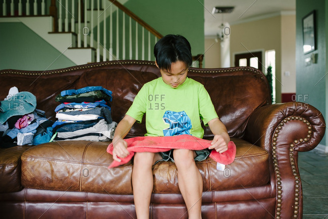 Boy folding freshly washed laundry while seated on the couch