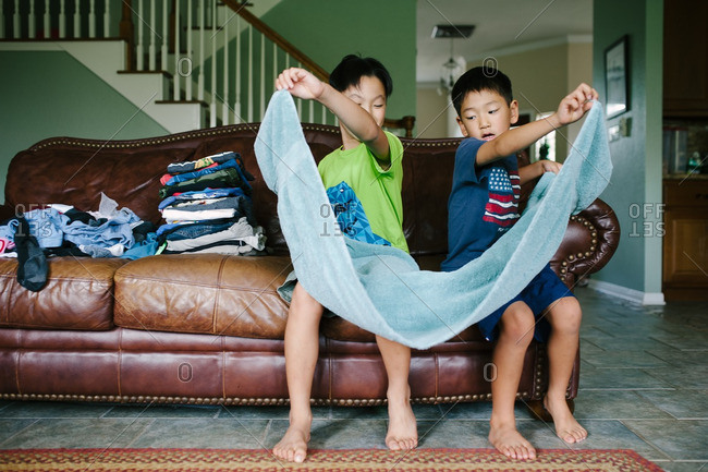 Boys working together to fold a freshly washed towel