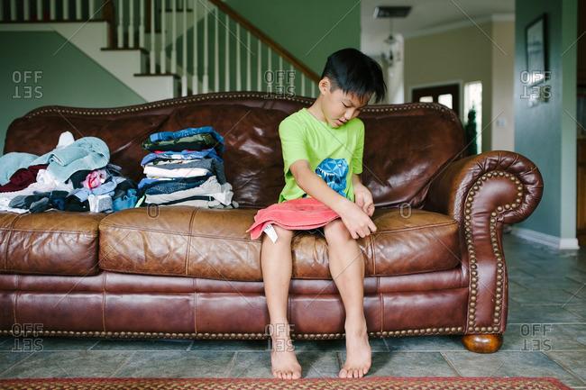 Boy helping fold freshly washed laundry