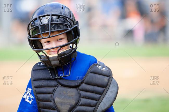 Portrait of a boy wearing baseball catcher's gear