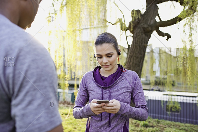 Woman checking her smartphone during a workout