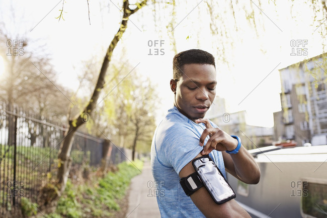 Portrait of an African American man adjusting a digital music player before a workout