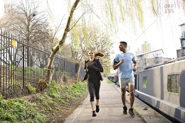 Couple running together along a canal in the city