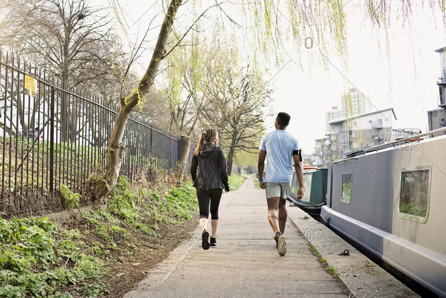 Couple walking together along a canal in the city