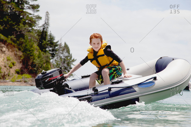 Boy steering speeding motor dinghy at sea