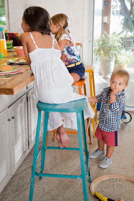 Two sisters at kitchen breakfast bar with toddler brother watching