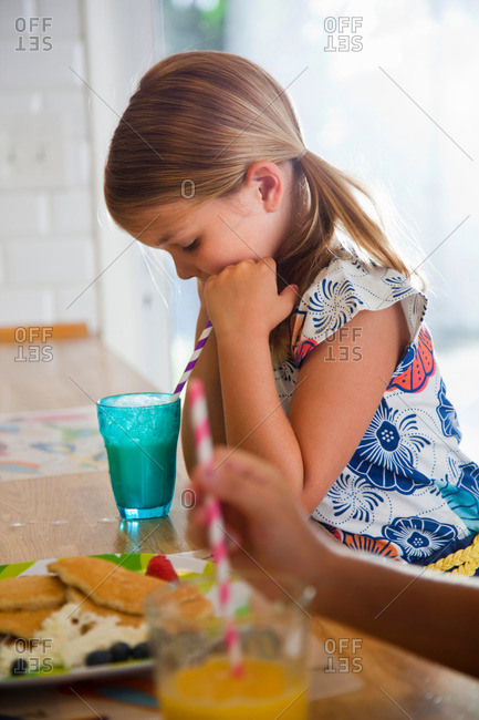 Two sisters drinking from straws at breakfast bar