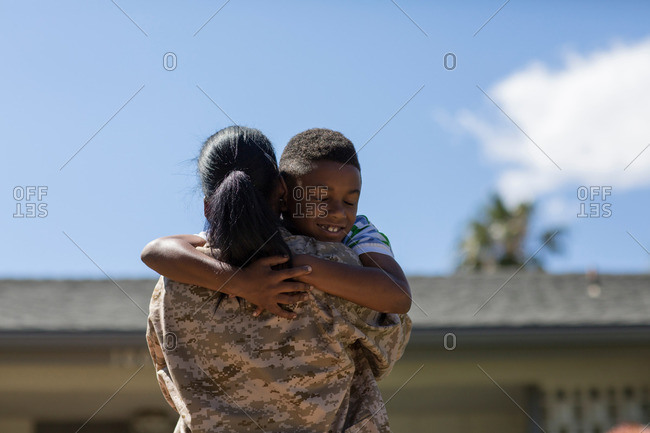 Rear view of female soldier hugging son on homecoming