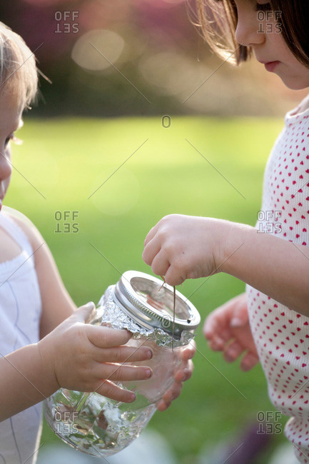 Girl and toddler sister putting green anole lizard in jar