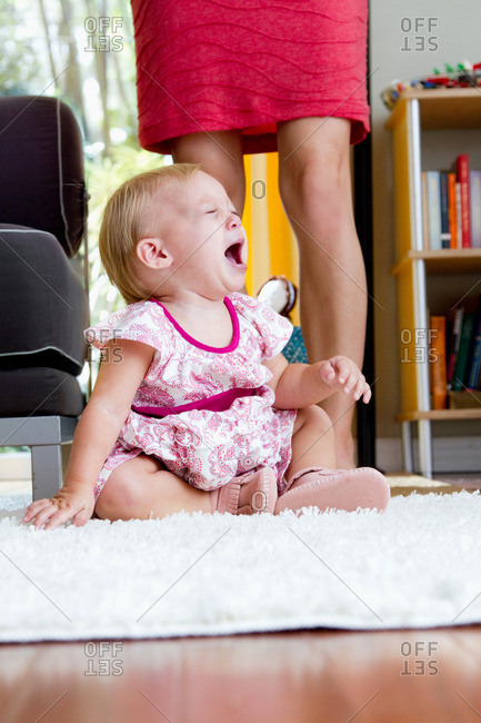 Legs of mid adult mother next to screaming baby daughter