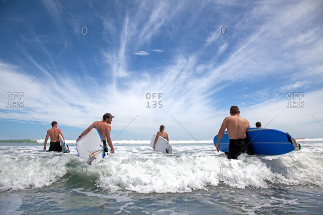 Group of male and female surfer friends wading into sea with surf boards