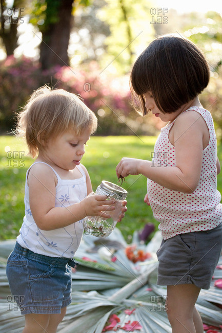 Girl and toddler sister with green anole lizard and jar in garden