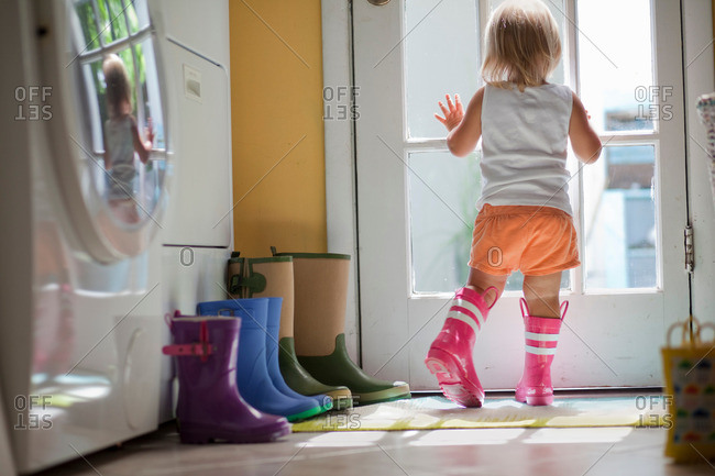 Female toddler wearing rubber boots looking out of back door window