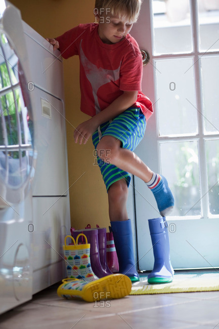 Boy putting on rubber boots at back door