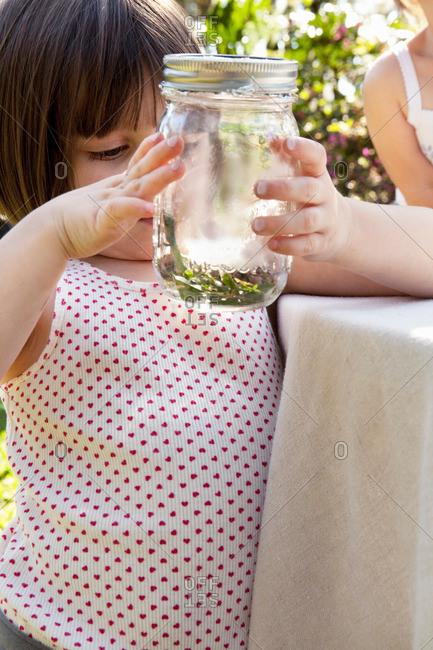 Girl holding jar with green anole lizard in garden