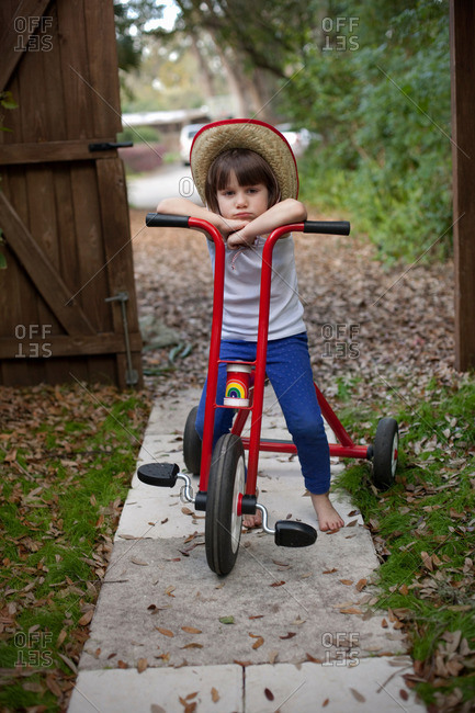 Portrait of four year old girl sitting on her tricycle in garden