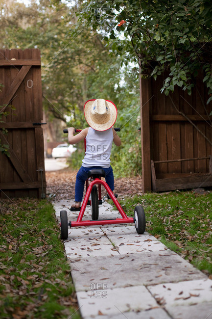 Four year old girl riding her tricycle out of garden gate