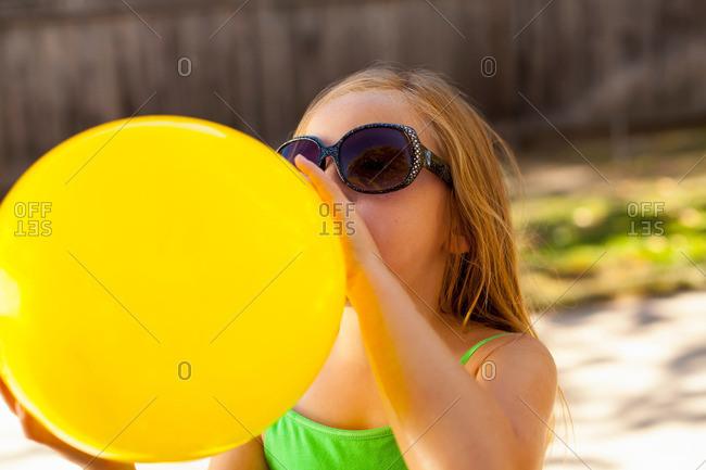 Girl inflating yellow balloon in garden